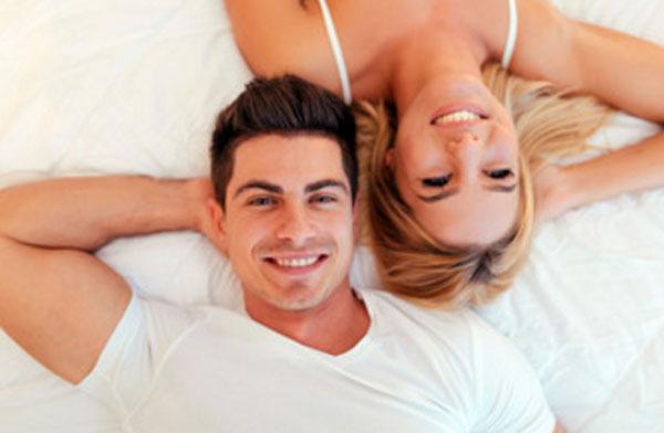 """Муж и жена лежат на кровати """"валетом"""", улыбаются"""