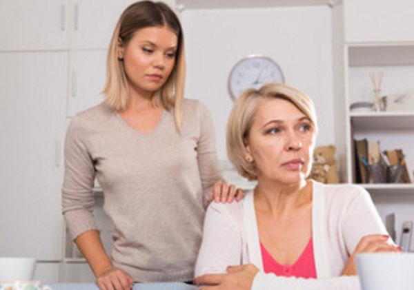 Дочка подошла сзади к сидящей за столом печальной матери