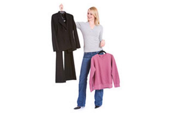 Женщина в одной руке держит вешалку с костюмом, в другой - вешалку со свитером