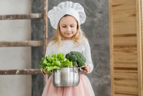 Девочка с колпаком на голове несет кастрюлю с овощами