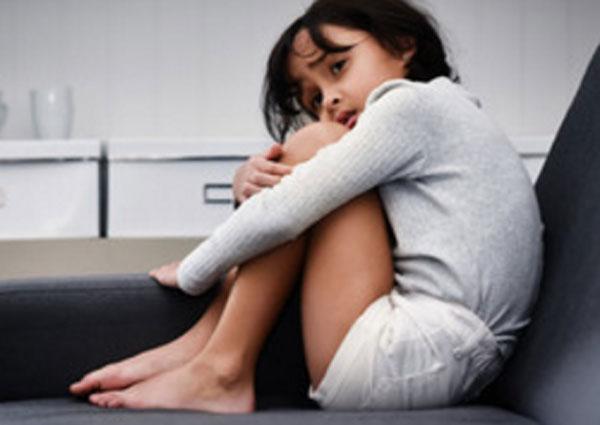 Ребенок сидит на кровати, подогнув ноги.