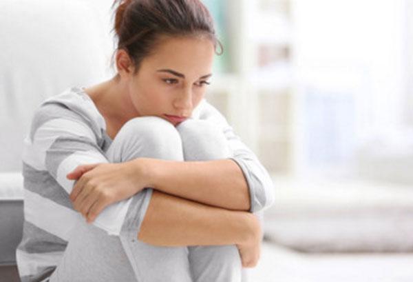 Расстроенная девушка сидит в задумчивости, поджав к себе ноги