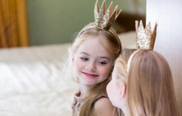 Маленькая принцесса смотрит в зеркало