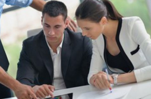 Грустный мужчина смотрит в планшет, рядом другие сотрудники