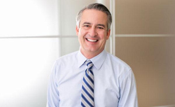 Мужчина в рубашке и с галстуком улыбается