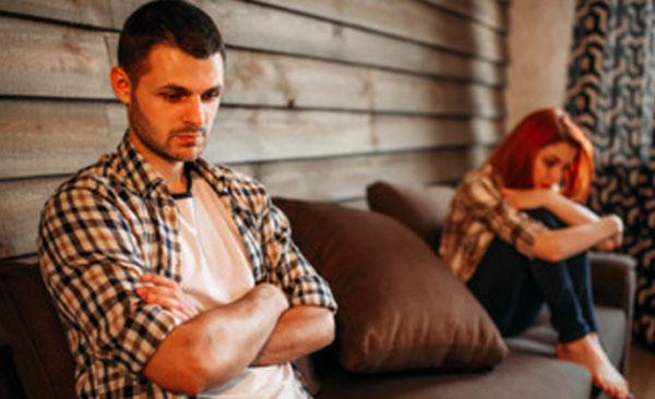 Муж и жена поссорились. Он грустный сидит в одном конце дивана, а жена - в другом