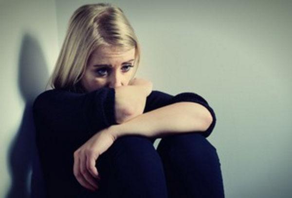 Грустная женщина сидит в углу