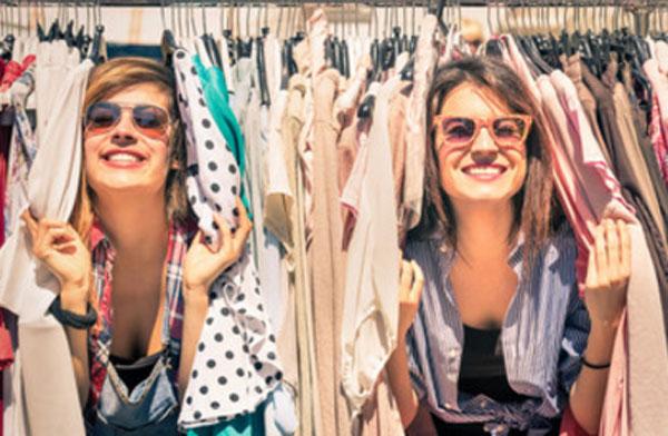 Две молодых женщины в солнцезащитных очках выглядывают из-за вешалок с одеждой