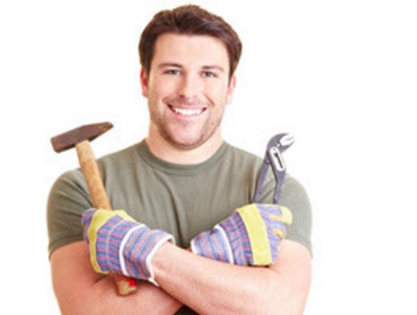 Улыбающийся мужчина в строительных перчатках с молотком и плоскогубцами в руках