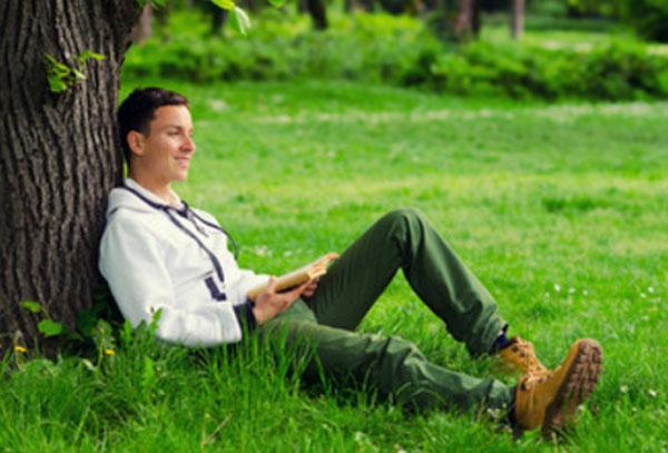 Счастливый парень сидит под деревом