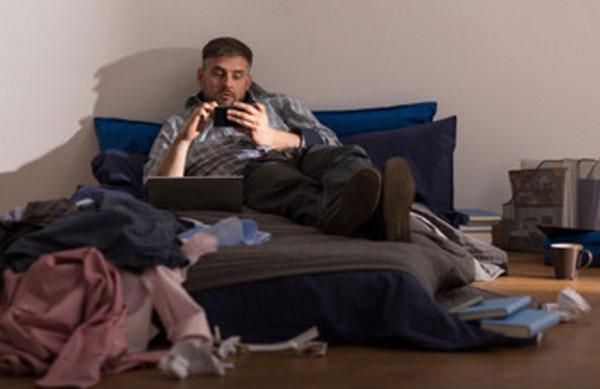 Мужчина лежит на кровати, вокруг беспорядок