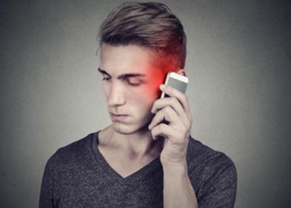 Парень держит возле уха телефон и молчит
