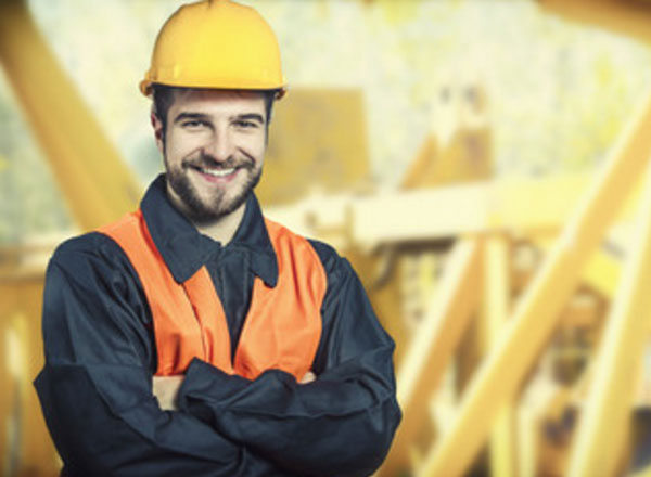 Мужчина на производстве, стоит в каске и улыбается