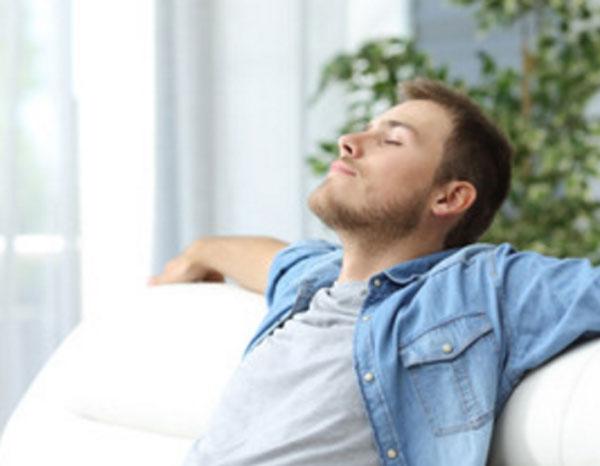 Расслабленный парень облокотился на спинку дивана