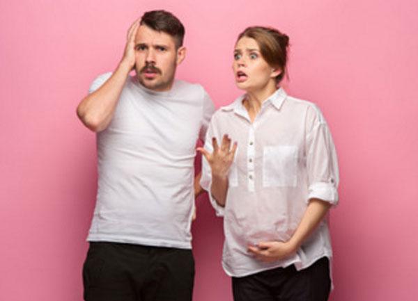 Беременная женщина что-то высказывает своему супругу