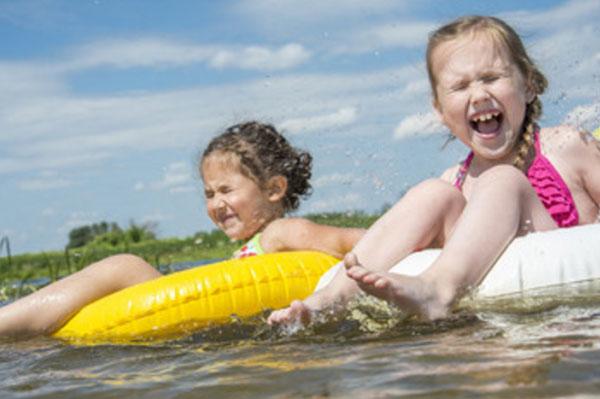 Девочки на плавательных кругах на воде, верещат