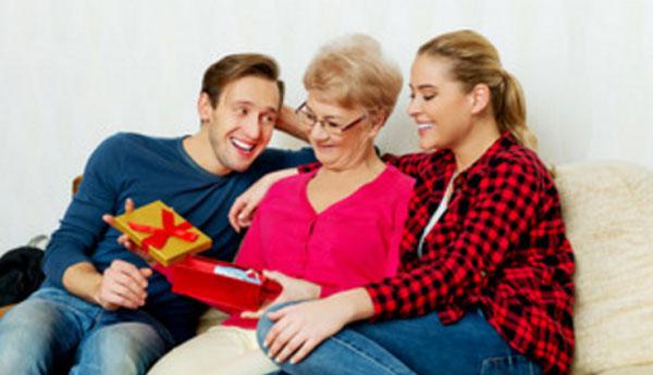Муж, жена и мама мужа сидят на диване. Маме вручили подарки