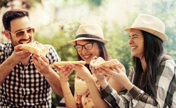 Подружки и парень едят пиццу на улице