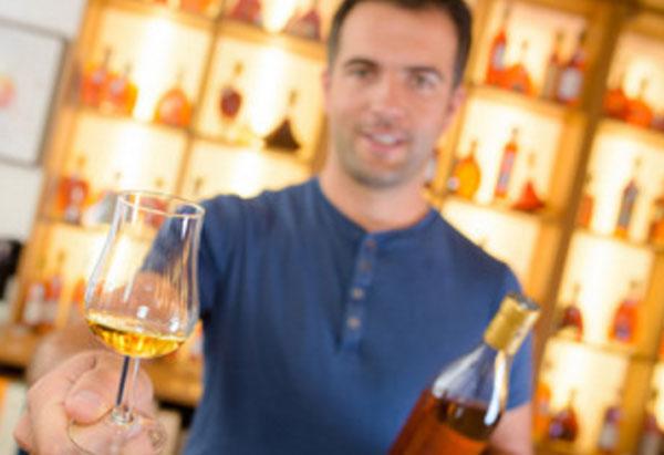 Мужчина держит в руке бокал со спиртным на донышке