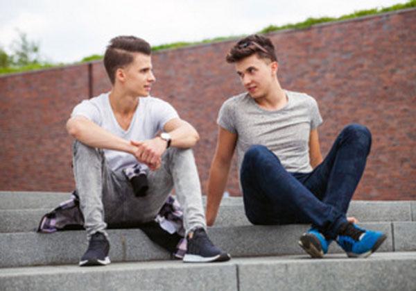 Два парня общаются, сидя на ступеньках