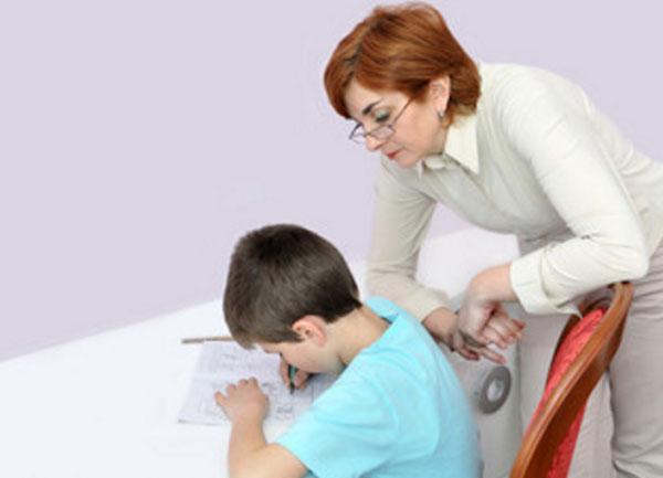 Мама стоит над сыном, следит, что он пишет