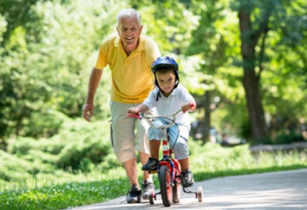 Дедушка идет за внуком, который едит на велосипеде