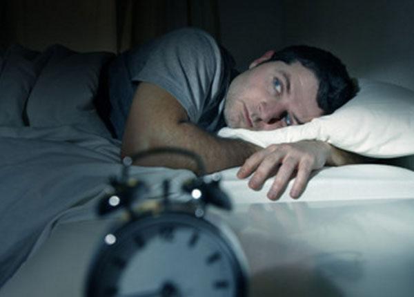 Мужчина напряженно лежит в кровати в темноте