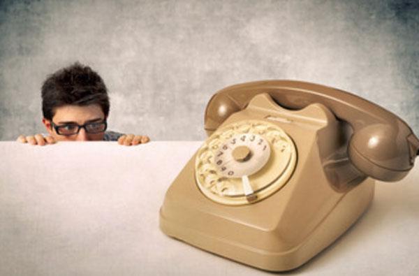 На переднем плане телефон. На заднем мужчина, который прячется
