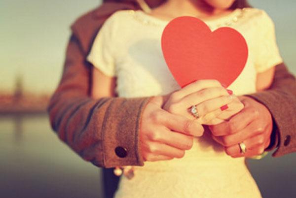 Мужчина сзади обнимает девушку, держит ее руки в своих, она держит картонное сердце