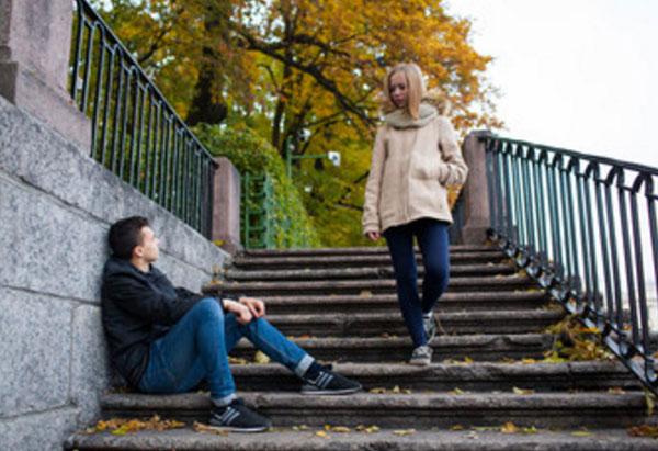 Парень сидит на ступеньках, мимо проходит девушка и смотрит на него