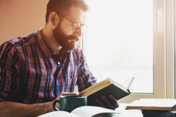 Мужчина читает, на столе стоит чашка чая