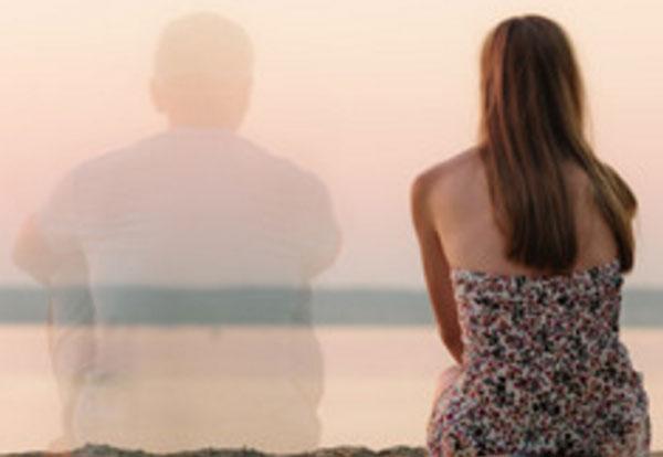 Девушка сидит на берегу. Рядом с ней прозрачный силуэт парня