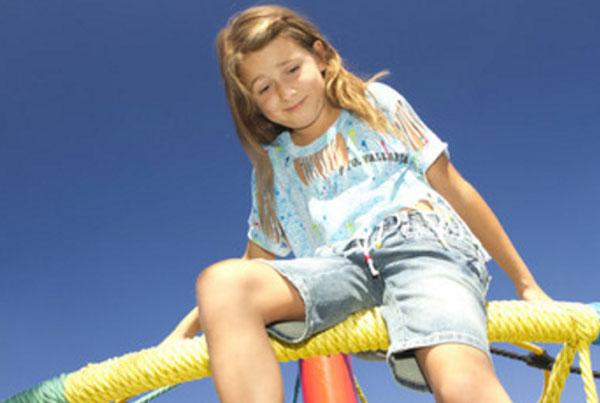 Девочка сидит на возвышенности и боится