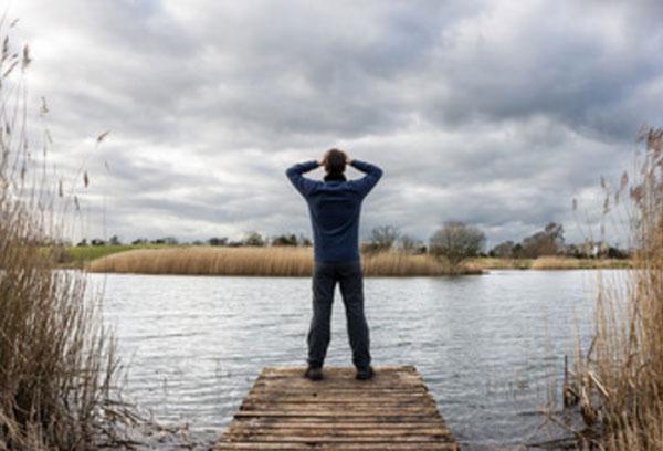 Мужчина стоит на мостике перед рекой. Держится за голову двумя руками