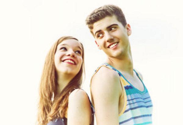 Парень с девушкой стоят друг к другу спиной и смотрят влюбленными глазами