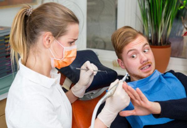 Парень с ужасом смотрит на руку стоматолога с инструментом, не дает к себе притронуться