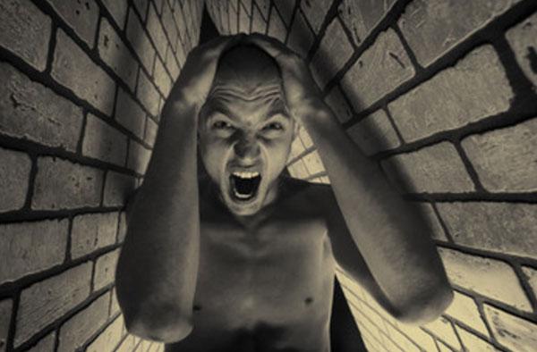 Мужчина в ужасе. Стоит в узком помещении