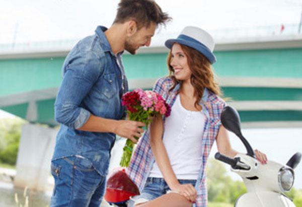 Парень признается в любви девушке, сидящей на мопеде.дарит ей букет цветов