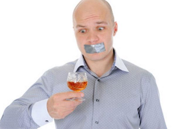 Мужчина держит в руке рюмку со спиртным. У него скотчем заклеен рот