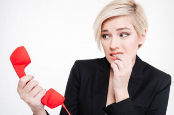 Женщина держит в руках трубку стационарного телефона. В глазах у нее страх
