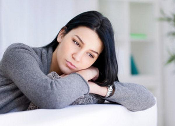 Грустная женщина сидит на диване