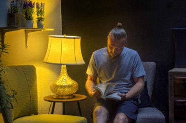 Мужчина листает книгу возле ночника