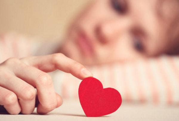Грустная девушка лежит и пальцем трогает картонное сердце