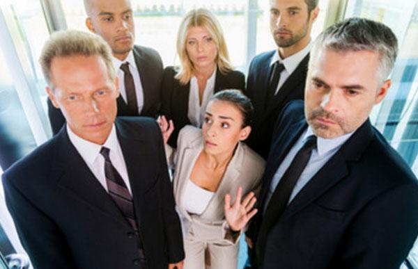 Женщина стоит в лифте с людьми. Она в панике