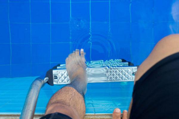 Мужчина опускает ногу в воду. Находится в бассейне