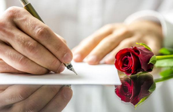 Мужчина пишет письмо. Рядом на столе красная роза