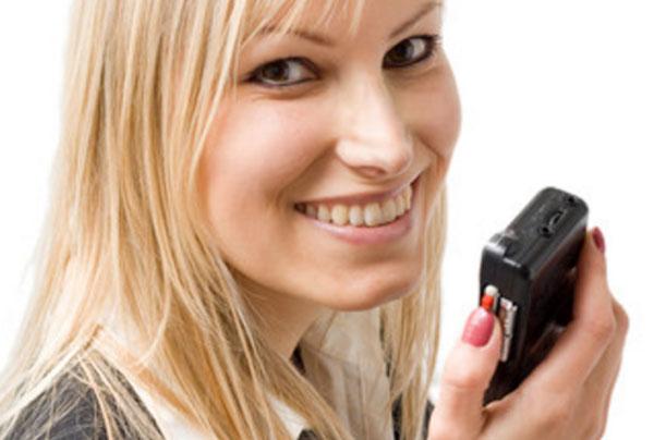 Улыбающаяся женщина держит в руках диктофон