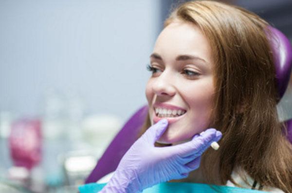 Девушка с белоснежной улыбкой на кресле у стоматолога