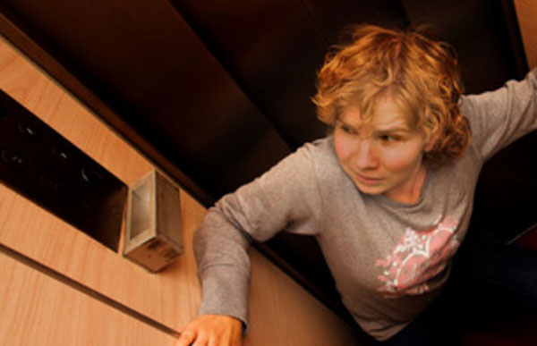 Женщина в ужасе, сидит на полу лифта