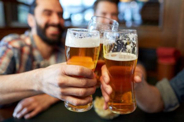 Мужчины поднимают бокалы с пивом